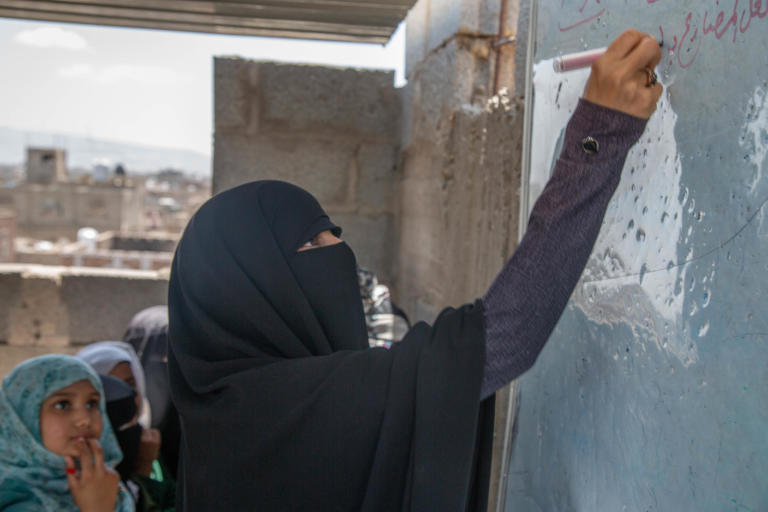 "Rahma Ahmed 32 years old a teacher at Yemen Al-Mustaqbal school in Sana'a – Bani Al-Harith district.  Rahma teaches Arabic lecture, she started her career in teaching since 2012 as a teacher. Her life was stable with her husband and her child Mohamed, 10 yrs. Before the conflict started, Rahma and her husband were able to afford the daily needs as the income could cover the house rent and food.   Since the conflict started, education sector in Yemen collapsed, Teachers who have not received regular salaries for two years, can no longer meet their most basic needs and have been forced to seek other ways of income to provide for their families. Rahma one of the teachers who haven't received a salary and she could stay seeing her son starving after her husband also left them because he could not afford anything for them. Rahma has skills on drawing, an alternative way to get income she draws scholastic arts and sells them for schools in a nominal amount 400-500 Yemeni Rial which's (1$) per piece.   ""Before the war, we were receiving salaries, somehow it's little but at least we can afford everything as prices were affordable. But now no salary and if we get the same amount of salary it will not cover 50kg of wheat… it's nothing.""  ""Sometimes, I borrow money to get my son a sandwich for breakfast and some stationary for my son, I want to keep him motivated after his father left us. I don't want to destroy his future.""  ""I use my skills on drawing to draw scholastic arts for the schools, I get around 1$ per piece, it not much, but I love doing it""   Despite all the challenging she faced, Rahma continues going to school and teaching the students. Her motivation is to educate the next generation who'd build her country and she believes that it not fair to let those children without education.   ""The motivation to come to school is to educate and build the next generation, and it's not fair to let Yemeni children without education no because of the salary, the salary is nothing. I want also to keep my son motivated to not leave the school.""   Rahma sees the students suffer the most, the student behaviors changed because of the war and the students become more violent and aggressive, in addition to that some of her students cannot afford the transportation or breakfast, they sometimes come to school hungry which make them unable to comprehend the classes and some cases fall down during the day because of hunger.  ""I remember one of my students has fallen down because she did not eat breakfast and she cannot afford""  ""I can see also some student cannot be active in the class because they eat only one meal per day according to my discussion with some students.""   ""Students also traumatized because of the war and they can no find a safe place to study.""   Rahma's son Mohammed 10, years old, 5th grade, He is the only child for her. Raham takes Mohammed every day with her to the school to save more money even if she has no classes to teach, they go together to the school to by walking. The school is one kilometer far away from the school it exhausting for her son.  ""I take my son every day with me to the school, in order to save some money, we share the breakfast together even if I don't have classes I stay until he finishes.""   School situation The school is a poor condition, small and it hosts more than 1500 students. The school building is basically a rental house and it has no school facilitations or yard for students. In addition to small classrooms with almost no desks. Some students take their classes on the roof of the school building due to a shortage of space.   ""The building is a poor condition; the classes are small and student set on the ground. The affect negatively on students. Some of them the study on the roof under the sun.""  ""The fear also from the diseases, the crowded place could be a place for spreading the disease.""   Rahma's dream is to become an artist, she wants to sell her artworks to help vulnerable people in Yemen and help them to get medical treatment. Also, she wants the war to end   ""I want to become an artist so that I can sell my arts and give the money to people in need especially who need medical treatment that causes by this war."" ""I wish the peace returns back to my country. I don't want to see children's future unknown.""     NRC is responding to Yemen Al-Mustaqbal School with European Union Humanitarian Aid fund by building new classrooms and desks, in addition, to conduct training for the teachers and creating temporary Learning Spaces (TLS). The students will be able to move the new building in the coming school year.   ""Thanks for the donor, we are really excited to move the new place, I am sure that the new build will be a motivation for the children and change to their behaviors.""  ""Students will have a place to learn and play, the new building has a lot of facilities that would help students to have a quality education.""  Photo Credit: Mohammed Awadh/NRC"