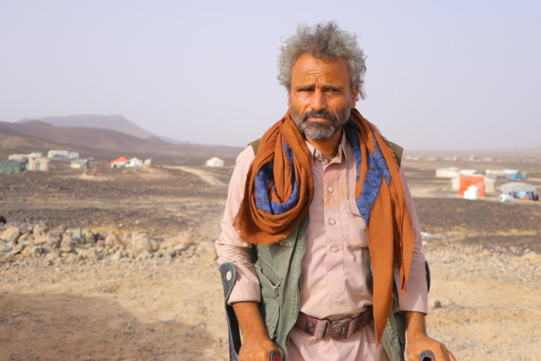 "On the 10 April, the same day the first Covid-19 case in Yemen was confirmed, Muhsen Ahmed Mahyoub was fleeing his home.   Muhsen's home village of Hareeb was a small and a peaceful one, not far from Sana'a city. On the farm he had inherited from his father, Muhsen kept goats and sheep, and planted corn, barley and wheat. He held on to this quiet life through five years of escalating violence. Even when a landmine took both his legs in 2016, Muhsen still steadfastly continued farming, thanks to the help of his children. The farm was his life, and his only source of income. How would his family eat, if they left?  But on 10 April, one day after a unilateral ceasefire was announced, the war finally forced him to flee.  First came the gunfire in the distance. When it grew closer, Muhsen called his wife and children together, and quickly rounded up the goats and sheep. Around him, other families were doing the same.   Muhsen hired a small pickup, loading his animals in the back, and struck out for the desert near Marib city. Here, a barren stretch of sandy land has in the last four months become home to 500 families from around Marib and Nihm.   It is known as Al-Swaidah camp, though there is nothing to mark it as such: no running water, no toilets, no electricity. It is just there.   Muhsen's family assembled a tent for themselves from iron pipes and plastic sheets. But despite these conditions, Muhsen is just glad to be safe. ""We felt we were the luckiest in the world when we arrived.""  Some families still have their goats and sheep with them. Muhsen has sold his animals to buy food and other basic items. ""In my village, I used to eat from my farm and sell the rest. But here we are dependent on organizations to help,"" he says. ""It is true that we can get some food from WFP, but it isn't enough.""   Muhsen is thankful to those organizations which have started to provide mattresses, water and food. But there is so much they still need, including latrines and proper shelter. Storms and floods have damaged several tents in the last few months.  ""Before the war, I used to wake up before dawn and walk to the fields and work until ten. Then I would walk to the market to buy some things, and return to have my lunch with family. We sat together in the afternoon to chew Qat and talk—usually about farming. Nowadays, we are thinking all the time how to get food, how to get water and how long we can stay here.""  Muhsen has heard about Covid-19 but doesn't consider it a threat for displaced people, as they have other, more pressing, worries. None of the displaced people in the camp have been taking any measures against Covid-19.  He has not heard of the ceasefire declaration. He has seen the families still arriving from surrounding areas, fleeing the ongoing fighting. And so far, the news from his hometown is that it has not stopped. ""The battles are still ongoing, so we can't return.""  Photo: Hassan Al-Homaidi/NRC"
