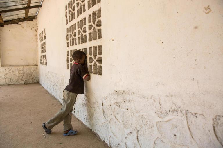 Boy, about 10 years old, looking in through a window. (Photo: Ingebjørg Kaarstad/NRC)