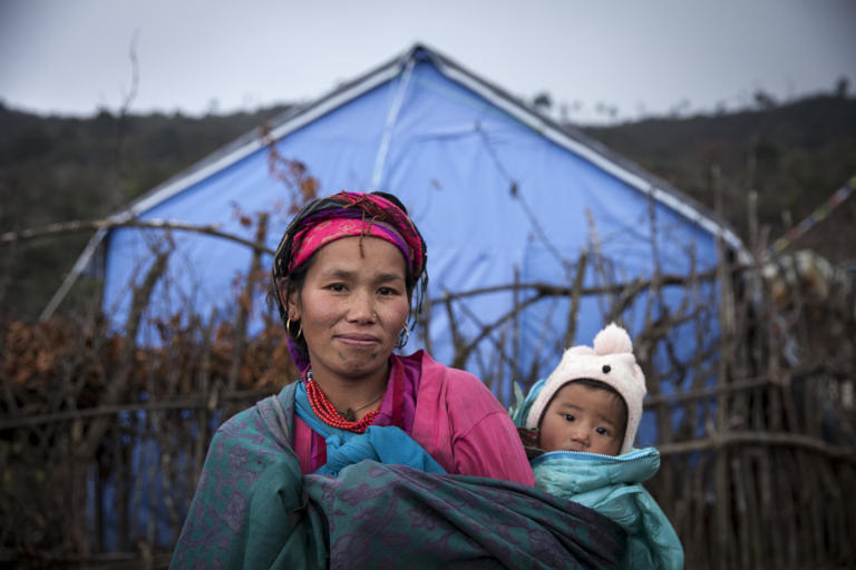 "Kanchhi Gole (30) had to run through a combined landslide and earthquake with her then three-month-old daughter Phurba (1) when the earthquake hit Nepal in April last year. (2015) Her husband was in the fields. They lost everything. Since then they have been living in Selang IDP-camp.  ""The landslide burried everything. It was so scary. Our home was destroyed. This place is safer. There are aftershocks, but we are not really scared. We are just worried that the snow will bury us, because the roof is not strong enough to hold the weight of the snow"", she says.  NORCAP experts working with IOM have distributed tents and tarps, and blankets to help shield against the cold. But the IDPs would like corrugated iron sheets for their roofs, to keep the snow out.  ""We don't have enough warm clothes. I only have two sets of clothes for my daughter. We are suffering, but at least we are alive. There is no other option"", she says. (Photo: NORCAP/Kishor Sharma)"
