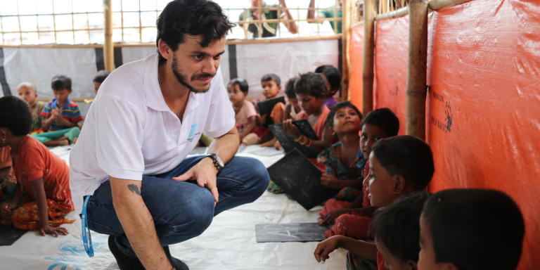 Henry Renna Gallano, education in emergencies expert, with Rohingya refugee children in a learning centre in the refugee camps in Cox's Bazar, Bangladesh. (Photo: Ingrid Prestetun/NRC)