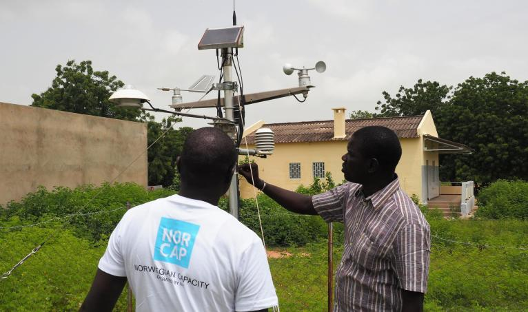 NORCAP climate expert Alioune Kaere and Djabel Ndiaye from the Senegal meteorological office, ANACIM, inspecting a weather station in Kaffrine, Senegal. (Photo: NORCAP/Ida Sem Fossvik)