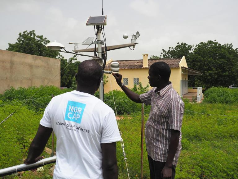 Diabel Ndiaye from the Senegal national met office, ANACIM, shows NORCAP climate expert Alioune Kaere one of the weather stations in Kaffrine department, Senegal.  (Photo: NORCAP/Ida Sem Fossvik)