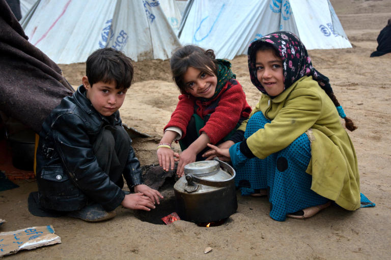 From right to left: Naseema, 9, Gul Ghotay's daughter and her friends, Dunya Gul and Mohammad Arif, warming their fingers in a cold day in Feristan IDP settlement in Qala-i-naw, Badghis. PHoto: NRC/Enayatullah Azad