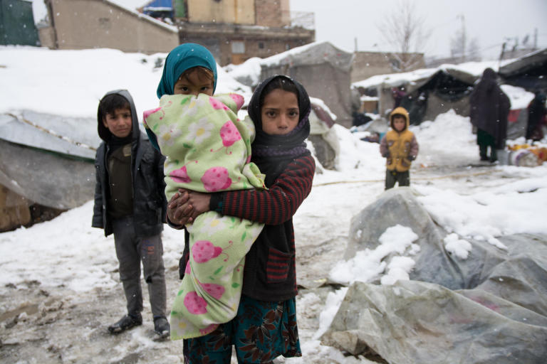 Nazia, 11, taking care of her little sister Palwasha, wrapped in a thick blanket in one of the informal settlements in Kabul. The children are experiencing their third winter in this settlement. photo: NRC/Enayatullah Azad