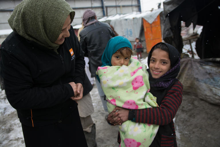 NRC's shelter technical assistant Masooma Qambari, talking to Nazia, 11, taking care of her little sister wrapped in a thick blanket in one of the informal settlements in Kabul. The children are experiencing their third winter in this settlement. photo: NRC/Enayatullah Azad