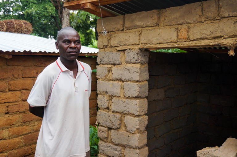 "Butunga Apimo, 46, from DRC Apimo has recently worked with NRC to build a new latrine for himself and his family. It's lockable both from the outside and inside, so that Apimo and his family can ensure their privacy and exclusive right to their latrine.  Apimo is happy to have received a latrine, but has his heart set on another need for his family: ""Can you bring us a water point as well?""  Photo: Guri Romtveit/NRC"