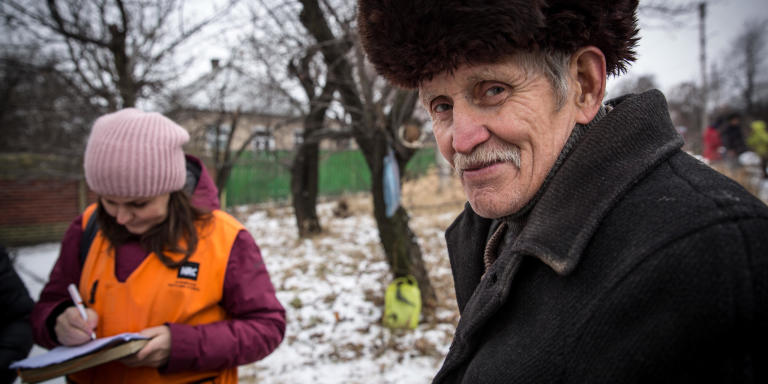 Anastasiia Karpilianska from NRC and Oleksii Tsylikovsky, 72, who is taking part in the Food for asset project in Hirske town. The project is focusing on rehabilitation  of community infrastructure and the beneficiaries are doing repair works on the worn-out water supply system in the main street in Hirske in return for monthly cash assistance.   Photo: Ingebjørg Kårstad/NRC