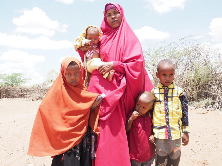 Halima Ahmed (24) and her children, Saadia (orange), Shueb (red) Mohamed (yellow) and 18-month-old son Mascud outside their home in Hagadera camp, Dadaab Refugee Complex, Kenya. Halima is planning to repatriate to Somalia with her four children and join her husband, who has already moved back to their country of origin after almost 10 years living as refugees.