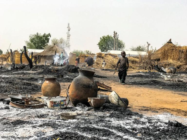 Large swathes of ashes and pockets of smoke can still be seen a few hours after a fire broke at a site for displaced persons in the town of Tungunshe, northeast Nigeria. A child walks by the scene. Credit: Hajer Naili/NRC