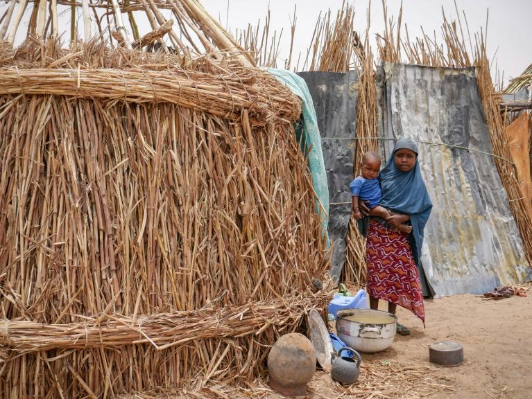 Aisha* holding her young brother while standing near a half-built hut that serves as a shelter to her family. Like over 1.9M Nigerians, this little girl has been displaced by an armed insurgency that began in 2009. Credit: Hajer Naili/NRC  *Name has been changed