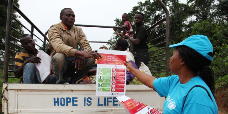 In April 2014 in Liberia, a UNICEF worker in the city of Voinjama, in Lofa County, distributes posters bearing information on the symptoms of Ebola virus disease and best practices to help prevent its spread. (Photo: NORCAP)