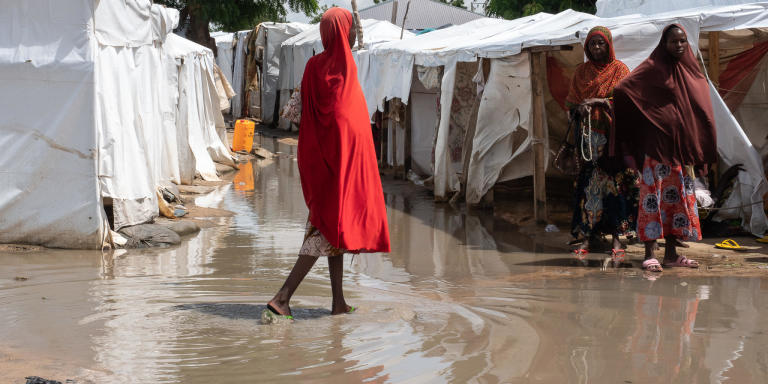 A young woman walks across a muddy path that resembles a river in Sharwari 5 camp in Maiduguri. The camp was one of the worst affected by the floods.