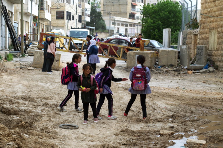 Children heading home from school pass the yellow steel gate at Qafisheh checkpoint in Hebron's Tel Rumeida neighborhood on 2 May 2019.  Photo: Ivan Karakashian/NRC