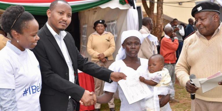 Women shakes hand man presenter her a birth certificate for her baby at a mobile birth registration exercise.