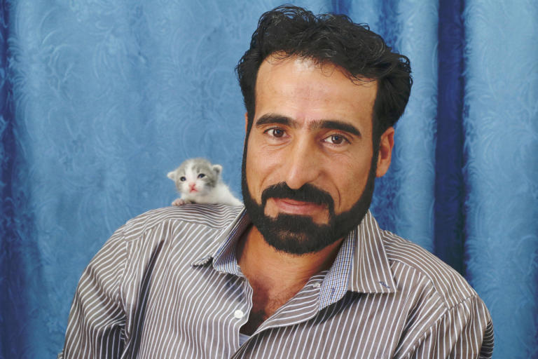 "Hashem, 38, a Syrian refugee who lives in Lebanon  Cats' names: Zaynoun and Zannoun (referred to a Syrian series he used to watch it)  ""I love cats since I was very young, but I encountered an incident which made me take the decision to raise cats. Once I was about to drive my work car at night, and I heard a cat meowing, she didn't stop meowing. I got off the car, and I saw my son, *Ahmad, attached to one of the tires, so I carried him, and took him home. The cat was warning me that something is wrong, she saved my son, and since then I always raise cats.  I used to have 12 cats here in Lebanon, but as we live in the mountains, the hyena ate most of them, only 5 are left now.  I love them like my children, I am very affectionate with them. It is something I can't explain in words, I love taking care of them, feeding them, and cleaning them.  I consider it a charity deed, God rewards us by taking care of the cats.  They complete my life, whenever I miss anyone of them, I go and look for them. They always follow me, and sit around me. They are a part of my family, they make me feel better emotionally.  If I go back to Syria, I will give them to someone I trust to take care of them, I don't think I would be able to take them with me to Syria, crossing the borders with them is not easy.""  Photo: Nadine Malli/NRC"
