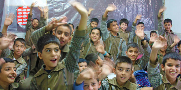 Students waving in a renovated classroom at Ahmadlou School in Afghanistan.