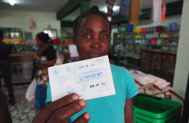 Beira, Mozambique (2019): Teresa Dolage holds up one of the vouchers she has received which gives her the opportunity to buy the items she needs from a local shop. The voucher is for 3.740 meticais (approx. $59) and the recipient has one month to spend the money. Most people spend it on food such as oil, rice, flour and ground nuts. (Photo: NORCAP/Ida Sem Fossvik)