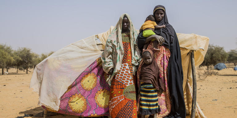 Aigachatou, a single mother and her children, standing in front of their makeshift tent after fleeing violence in Timbuktu in Mali.   Photo: Togo Moise/NRC