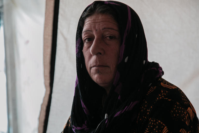 "Sorya Ahmed, 55, a grandmother from Ras Al Ayn. When Turkey announced their military operations in north east Syria she moved to different locations hoping that the situation would calm down, however things were escalating and the fighting was reaching them from one village to another. Eventually, Sorya and her family decided to leave Syria and seek refuge in Kurdistan Region of Iraq. Sorya has been displaced three times during eight years of war but this time was more horrifying than any time before.  ""We saw people burning in front of us. We escaped running over their dead bodies, there were no safe routes to escape, and they did not secure a road for civilians to leave."" ""We were 23 people; there were kids, women and young men with us. The smugglers were asking for a big amount of money. We did not have any money but we had my son's car, so we gave them the car instead of money."" ""At the border, we walked for around six hours. We were so scared that ISIS or anyone else would attack us. All of these children were with us without water and food."" ""On the way, we did not know who we are dealing with. Even men started to get scared because we no longer knew where we were going."" ""There is nothing to go back to, they burnt my house, and in Ras Al Ayn the original people of the area have left (now is full of Arabs and people from other areas). Even if I eat soil here I would not go back to Syria.""   Photo: Alan Ayoubi/NRC Date: 02 December 2019"