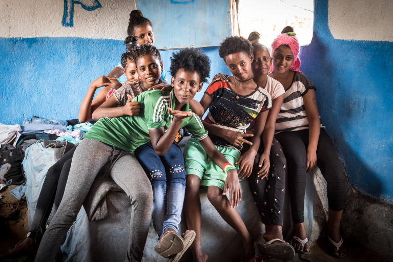 "Winta, 16 years old, Furtuna, 15, Lidia, 14, Fiyori, 16, Fiyori, 14, Weyni, 15 and Adkonet, 12 live together in a house in Hitsat refugee camp just outside Shire, a district in northern Ethiopia. The camp houses about 10,000 refugees from Eritrea. Most of them are minors, and about one in ten have fled alone.   The waiting room  Inside two small houses in a refugee camp in northern Ethiopia, seven girls and three boys wait for the Crown Prince Couple of Norway to visit.  All the children fled across the border from Eritrea, alone. ""Off course we miss our families, but we cannot return now,"" the children say.  It's lunchtime and 15-year-old Furtuna sits next to a pot, stirring with all the strength she has. A sauce of tomatoes, paprika and onion simmer inside. She is preparing food together with the eldest children, while the youngest girls have other tasks, like fetching bread or cleaning. The seven girls, who live in the house together, didn't know each other before they came to Hitsats refugee camp.   ""Now, we're like sisters,"" Winta says. For almost two years, the 16-year-old has stayed in the children's collective run by the Norwegian Refugee Council (NRC). ""Our friendship means a lot now.""   The room is no larger than 20 square metres, yet the seven girls use it as a bedroom, a kitchen and a living room. They also share the three beds. On the left side of the house lives an adult who is responsible for the girls, watching out for them and helping them when needed. On the right side of the house live six boys who also fled Eritrea to Ethiopia, alone.   As one of the eldest, Winta explains why they left their home country: ""We're all afraid to end up in the military and to lose the opportunity to get education. In the military you never finish and you have no choice. They come to get you, perhaps in the middle of the night. That's why many of us had to leave.""  The girls crossed the border to Ethiopia on foot, all alone. ""We heard people were shot on the way. In school, they told us that many girls were raped while trying to get away,"" says Winta. The other girls nod their heads in affirmation.   In the camp, the children attend school and get food. The girls are happy to live safely in the neighbouring country. ""The very best is that we don't have to be afraid anymore. And we have the opportunity to go to school and learn,"" Winta says.   The next door boys are 12, 14 and 15 years old. They have the same stories as the girls – grateful to be in safety, to escape the endless military service and to have the opportunity to go to school.  ""The education helps us grow and to make us stronger,"" says 15-year-old Meyhaw. He came to the camp five months ago.   When you ask the children if they have relatives in Europe, they all nod their heads. Uncles in Sweden and brothers in Germany. In the boys' house, they plan to go further abroad.   ""We're thinking that we have to travel to Sudan, Libya and then Europe. But for now it's too strict, so in the meantime we're happy to get more of an education,"" says Meyhaw.   The girls are not quite convinced as the boys about leaving Ethiopia. ""I have a brother who left with a cousin, but only my brother made it over the sea,"" says 15-year-old Weyni. ""There are days when all I want is to travel, but then I feel it's hopeless. We know how dangerous it is.""    For now, the children want to stay in the children's collective. The boys love their soccer practice and some of the girls have recently joined a drama group. If they were to wish for something better in life, they would wish for electricity to do homework. They would wish for some new clothes and maybe a cinema, so they could watch movies and forget about reality for a while.   Photo: Beate Simarud/NRC   Facts and figures:  Eritreans are the third largest group of refugees living in Ethiopia, with 37,321 refugees currently registered in refugee camps in the Shire area camps.   Currently there are 163,281 Eritrean refugees in Ethiopia.  It is estimated that nearly 40 per cent of Eritrean refugees leave the camps within the first three months of arrival, and 80 per cent leave within the first year, with significant numbers of the population departing irregularly from Ethiopia to third countries – often with the assistance of smugglers and at great risk to their lives.   The population in the Shire camps is unique, with a large number of children below the age of 18 and unaccompanied children.   As of June 2017, 72 per cent of the refugees living in Shire were under the age of 18, including 4,725 unaccompanied and separated children, representing approximately 11.5 per cent of the total refugee population.   Unaccompanied and separated children live in a variety of care arrangements, including community care, foster care, or family-based care."