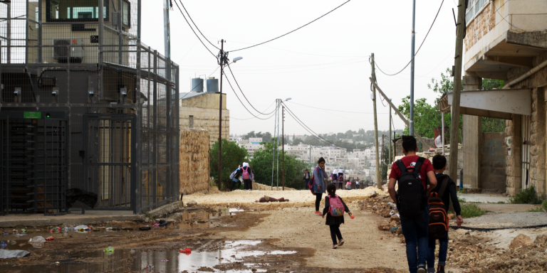 Children walk past Qafisheh checkpoint on a muddy road on their way home from school in Hebron's Tel Rumeida neighborhood on 2 May 2019.  Photo: Ivan Karakashian/NRC